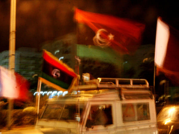 Libyan flags fly above the cars lining the streets of Benghazi.