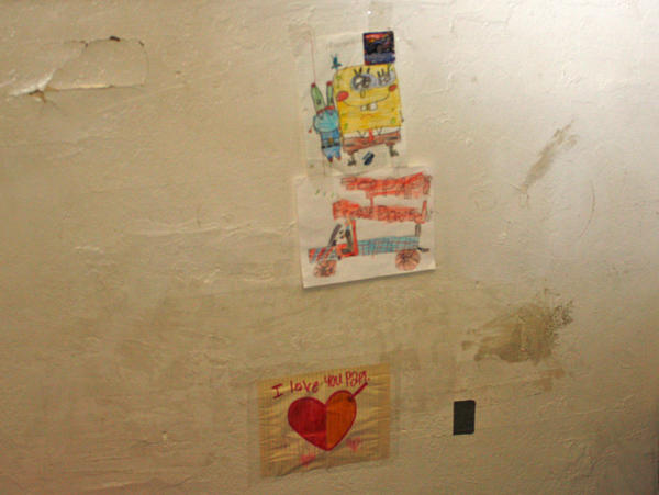 """David Jimenez, 7, patches up holes in his East Oakland, Calif., apartment. The bottom sticky note says, """"I love you Papi."""""""