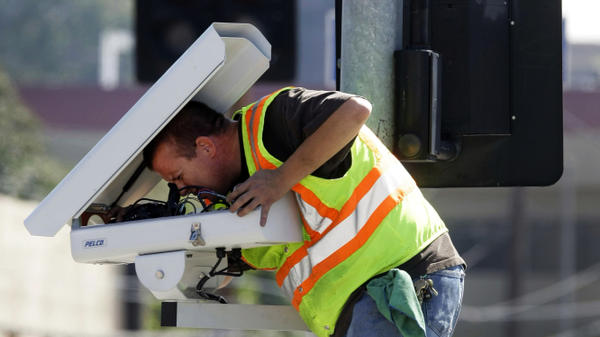Across the country, fed up drivers are fighting back against traffic cameras that target motorists who speed or run red lights. In Los Angeles, technician Charles Riggings services a traffic camera in 2010.