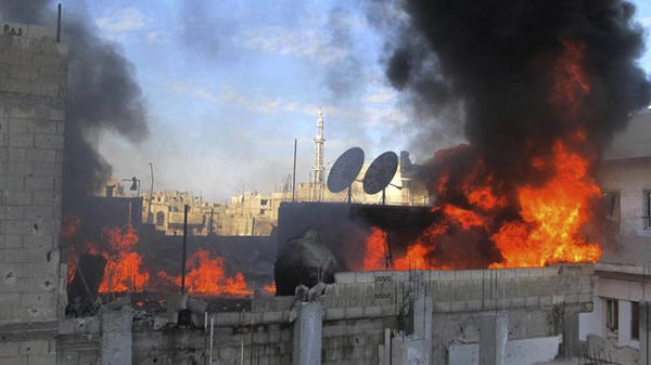 Flames rise from a house, the result of Syrian government shelling, in the Baba Amr neighborhood of Homs, Syria, on Wednesday, in this image provided by citizen journalists to the Local Coordination Committees.