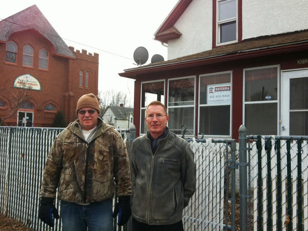 Dan Grohs (left) with real estate agent Pat Paulson in front of a foreclosed Minneapolis home. Grohs hopes to buy the house with cash.