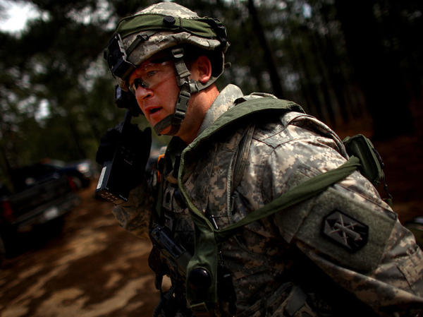 Lt. Col. Mark Schmitt, who will be among a group of U.S. military trainers heading to Afghanistan soon, calls out orders during a mock attack on the model Afghan village at the U.S. military base in Fort Polk, La.