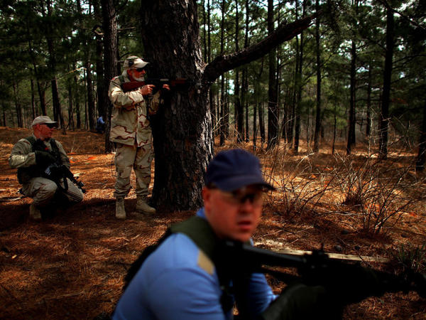 Role players from the Afghan National Army, in tan, and Afghan National Police, in blue, take up positions during a training exercise in a mock Afghan village in Fort Polk, La.