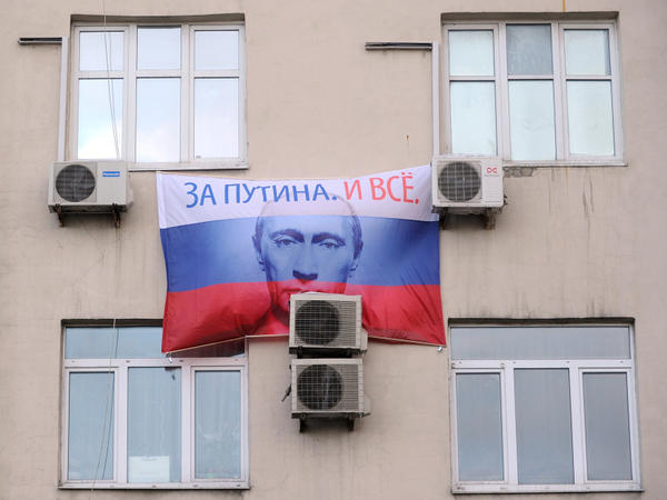 "A portrait of Russian prime minister and presidential candidate Vladimir Putin, bearing the slogan ""For Putin! And That's It!"" hangs on a building in Moscow."