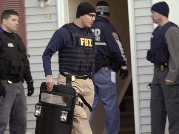 Law enforcement agents raid a home where the occupants are suspected of selling drugs last month in Middletown, N.Y. For three months, court papers say, authorities tracked them using wiretaps and cameras set up on telephone poles and trees.