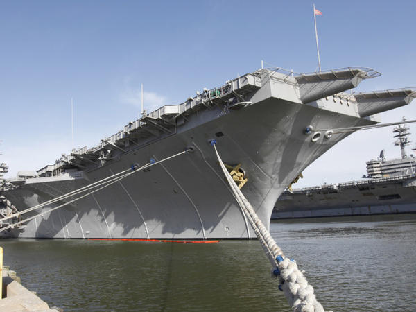 The nuclear powered aircraft carrier USS Enterprise sits at the pier as sailors move supplies and equipment in preparation for the ship's final deployment.