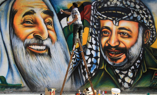 Palestinian artist Mohammed al-Dairi paints a mural of late Palestinian leader Yasser Arafat (right) and late Hamas leader Sheikh Ahmed Yassin (left), in Gaza City. Hamas leaders are divided on what direction to take the Islamist movement, with some calling for reconciliation with Arafat's Fatah movement.