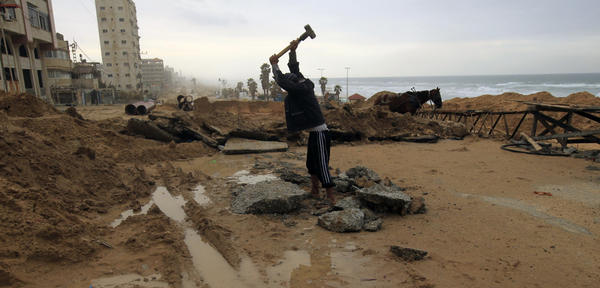 A Palestinian youth breaks up stones for construction in Gaza City. Despite restrictions on imports including building material, the area is going through a construction boom.