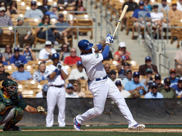 Matt Kemp of the Los Angeles Dodgers hits a RBI single against the Oakland Athletics during a spring training game at Camelback Ranch on March 8 in Glendale, Ariz.
