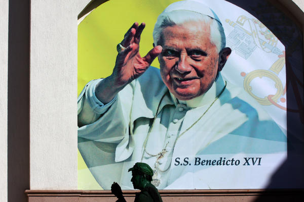 Pope Benedict XVI is expected to speak out against drug violence during his visit to Mexico, which begins Friday. Here, an actor is shown in front of a poster announcing the pope's visit Wednesday in the Mexican city of Leon, Guanajuato state.