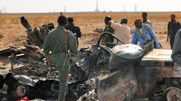 Sudanese troops stand next to a burnt-out military vehicle in the oil center of Heglig after clashes with South Sudanese forces Wednesday. Recent fighting has raised fears of a renewed war.