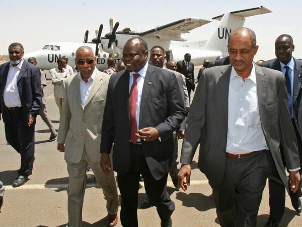 A delegation from South Sudan, headed by Pagan Amum (center), walks with Sudan's Idris Mohamed Abdul-Gadir (right) in Sudan's capital, Khartoum, on March 22. The delegation arrived for a summit between the leaders of the two countries, but the meeting was postponed due to recent tensions.