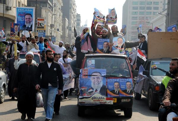 Supporters of an Egyptian Islamist candidate hold his posters as they drive through Cairo on Friday. If Abu Ismail is elected he plans to apply a strict interpretation of Islamic law.