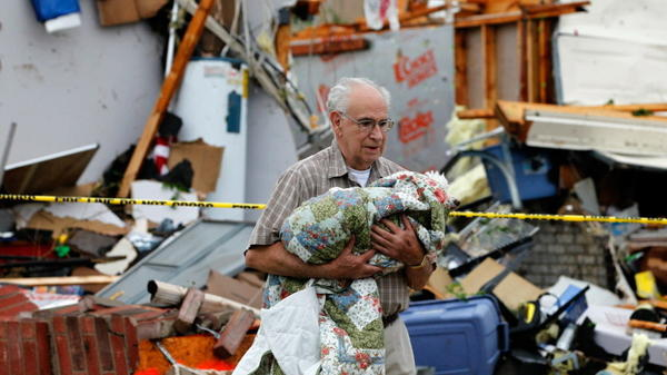 In Arlington, Texas, Tuesday afternoon, David Lowe carried his daughter's dog, Phoebe, away from the rubble.