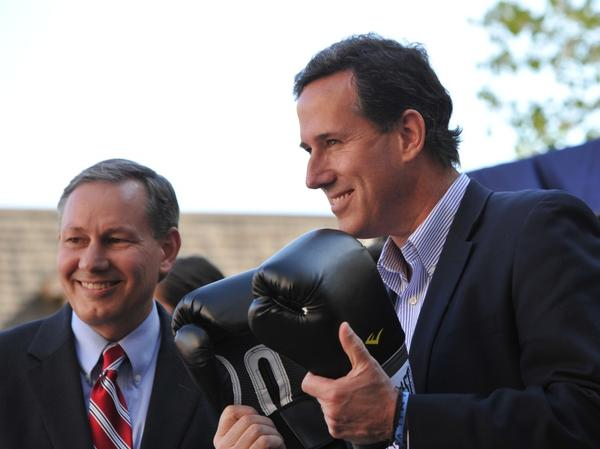 Rick Santorum speaks Wednesday in Hollidaysburg, Pa., holding  boxing gloves given to him by Pennsylvania State Sen. John Eichelberger (left). On Thursday, Santorum met in private with a group of conservative leaders to discuss next steps in his campaign.