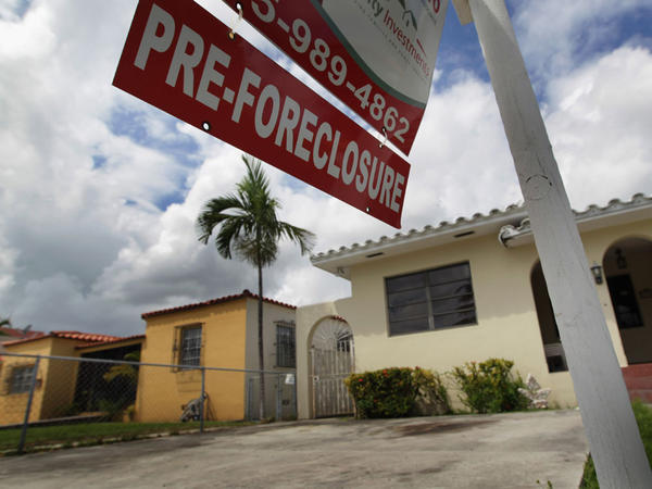 A pre-foreclosure sign is seen in front of a home in Miami. Supporters of a plan to reduce the principals owed by many homeowners facing foreclosure say it would prevent larger losses and keep people in their homes.