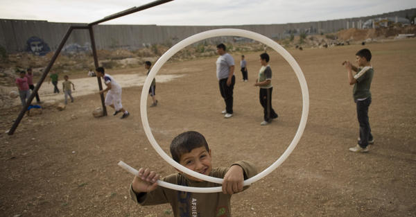 Palestinian children play next to Israel's separation barrier in the West Bank town of Abu Dis in 2011. As peace talks between Israel and Palestine remain at a standstill, people are looking to other possible solutions.