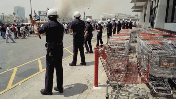 Los Angeles police form a line to keep a crowd from entering a building on April 30, 1992. Twenty years after the L.A. riots, most civil rights and community groups give the LAPD high marks for progress.