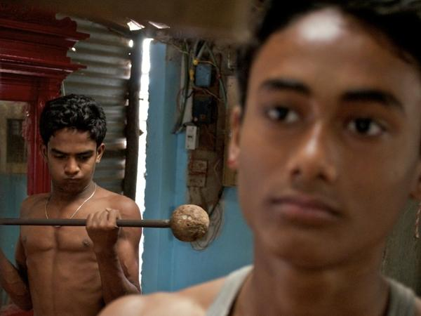 Sumon Mondol, in the foreground, works out at Mandohar Aich's traditional iron gym in Kolkata, India.