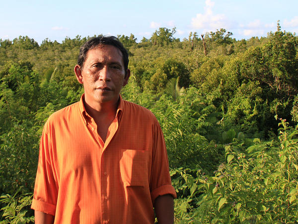 Rignolda Jamaluddin, a local marine scientist, stands in front of the mangrove forests of North Sulawesi that he has worked to rebuild over the past two decades. Part of his strategy included educating villagers on ways they would benefit from not cutting down the trees, such as making alcohol, sugar and furniture from the trees.
