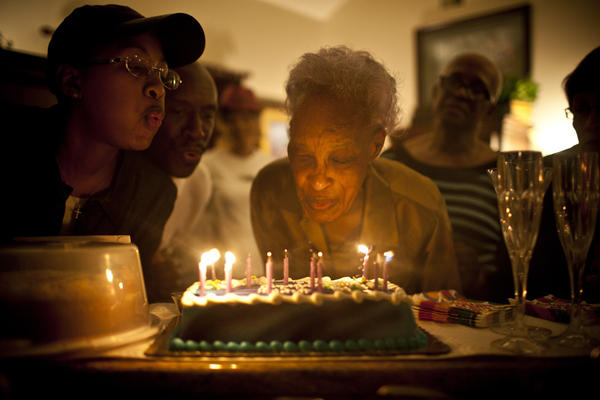 Ida Christian gets help from her granddaughter, Yolanda Hunter (left), in blowing out the candles on the cake celebrating her 89th birthday.