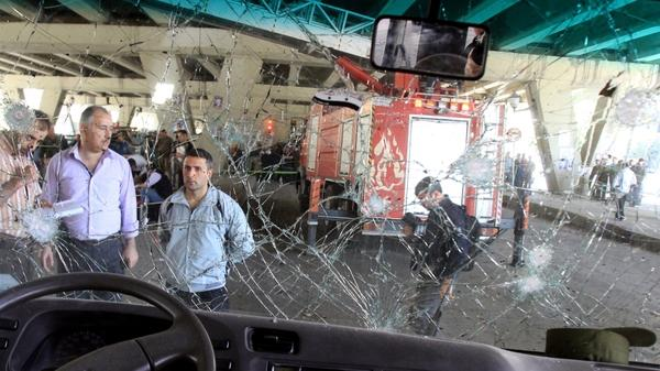 Syrians appear behind the damaged windshield of a minibus as they inspect the site of a blast in the central Midan district of Damascus last month. A new jihadist organization in Syria claimed responsibility for the attack.
