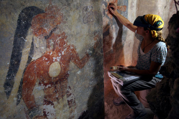 Conservator Angelyn Bass cleans and stabilizes the surface of a wall of a Mayan house that dates to the ninth century. The figure of a man who may have been the town scribe appears on the wall to her left.