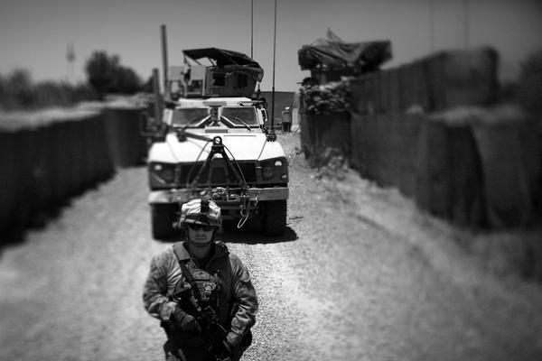 Marines guide an armored vehicle into Marjah's government compound. The Marines meet regularly with police officers and government officials who control the area.