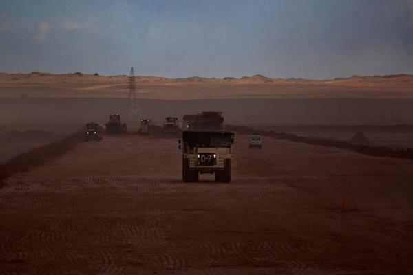 Trucks haul massive loads of dirt along an Oyu Tolgoi road.