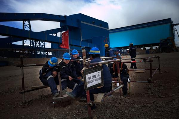 A group of Chinese workers takes a smoke break at Oyu Tolgoi. The company has imported thousands of skilled Chinese workers to help finish the mine infrastructure.