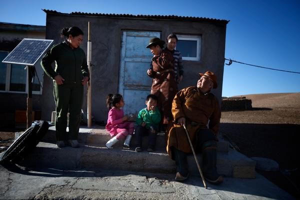 Mijiddorj Ayur (right) sits with his extended family outside his house in South Gobi. He wears traditional clothes, including boots with curled-up toes.