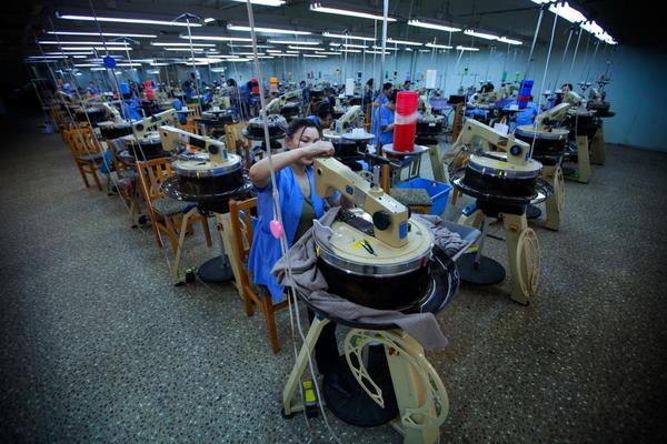 The circular machines on the factory floor are used to make ribbed cloth and sweaters.