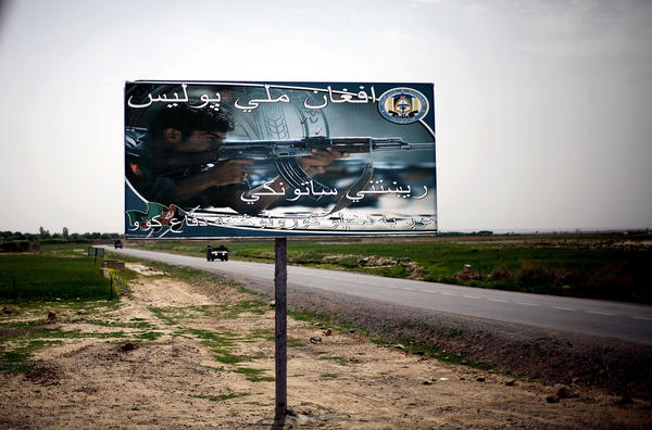"""A billboard reads """"Afghan National Police: The real guardian. We defend our own homes."""" It sits next to one of the main roads leading in and out of an area where the local population supports the Taliban."""