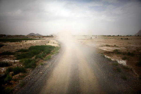 Dust fills the air in the wake of a U.S. Army vehicle as it rumbles down a gravel road in southern Afghanistan.
