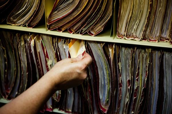 The mystery ailments have prompted the clinic to relocate to a new site 30 minutes away. Here, a staffer sorts through patient files that will need to be moved.