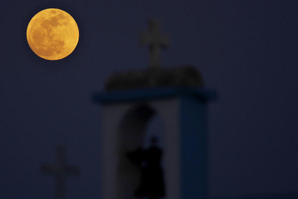 The full moon rises behind a steeple with cross of Ayia Thekla (Saint Thekla) Christian Orthodox church near coastal resort of Ayia Napa, Cyprus.