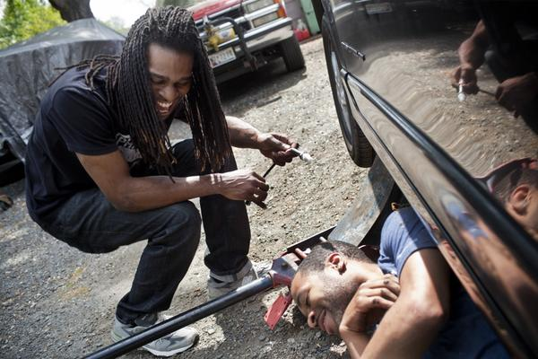 """Nicholas (left) laughs with his childhood friend Corey Buford while they work on Nicholas' car. Nicholas has briefly abandoned his music aspirations and is close to getting a job with Comcast to install cable. """"The money is more important,"""" Nicholas says. """"I need something that I can contribute [to the household] with."""""""