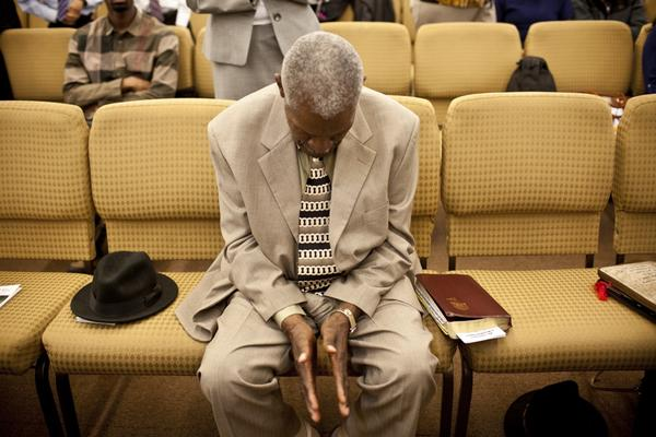 """Franklin prays during Sunday worship. """"I got aches and pains but I can still walk around,"""" he says."""
