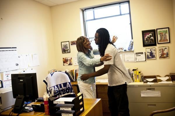Natasha hugs her 24-year-old son, Nicholas McDonald, at her office. Not only does she care for her father, but Nicholas also lives in the home.