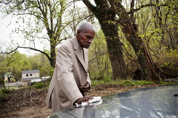 Franklin wipes pollen from the family car in their driveway before heading to church on a Sunday morning. He talks about missing his independence, including driving.