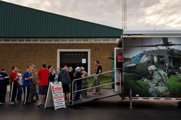 Army recruits form a line outside an Army National Guard trailer where they can watch films depicting combat.