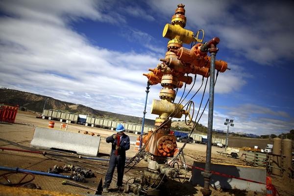 """A worker with Encana Oil and Gas stands near a natural gas """"Christmas tree"""" used in the natural gas extraction process."""