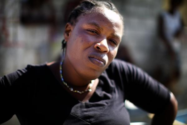 """Nadia Simone stands in front of her house in Cite de Dieu. She says she has been trying to get a trash-clogged ditch next to her house drained because she knows it brings cholera right to her doorstep. Last year cholera made her young daughter very sick. """"I don't want cholera to come back to my house,"""" she says."""
