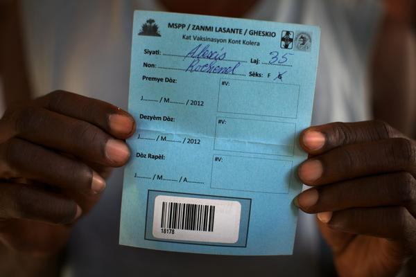Rice farmer Alexis Rochenel, Fifi's husband, shows his blank cholera vaccination card. People will need two doses of vaccine spread over several weeks. Health workers could have been finished with the first round of vaccinations by now. But they're still waiting for the government to sign off on the project.