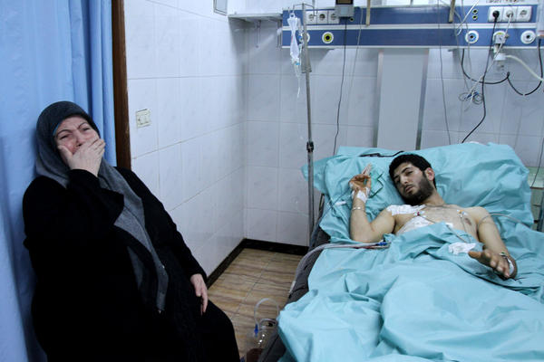 A woman weeps next to a man injured in clashes in the port city of Latakia on March 27.