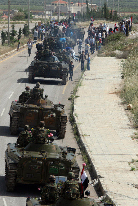 Syrian army troops drive out of the southern city of Daraa on May 5, following a crackdown on protests.
