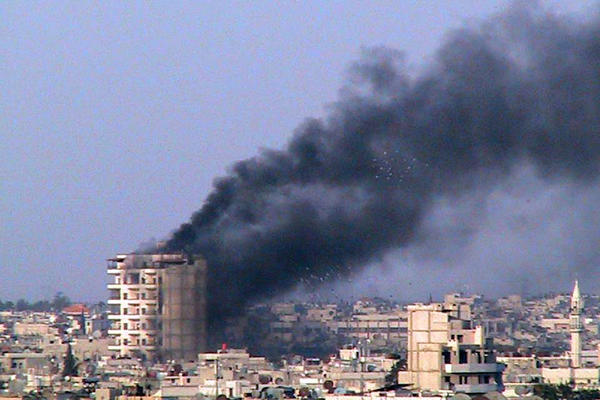 Smoke rises from a building shelled by the Syrian army in Homs on March 9.