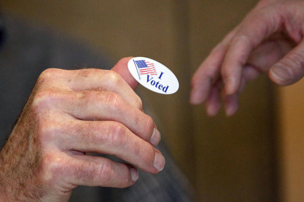 "Madison United Methodist Church precinct worker Bob Shirley hands a ""I Voted"" sticker to a voter in Madison, Miss."