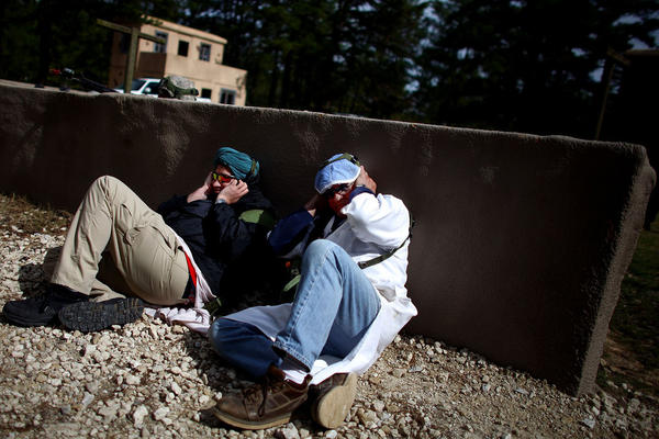 Afghan role-players cover their ears and hide behind a wall during a gun battle.