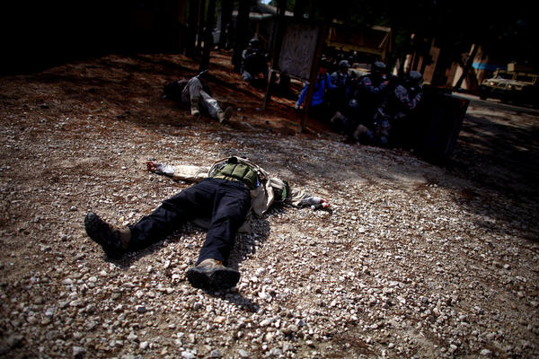 A mock suicide bomber plays dead in the middle of a shootout.